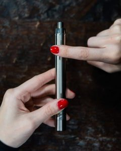 Hands with red finger nails holding the Terp Pen XL upright.
