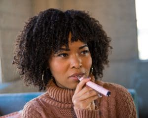 Woman taking a hit from a pink dab pen.