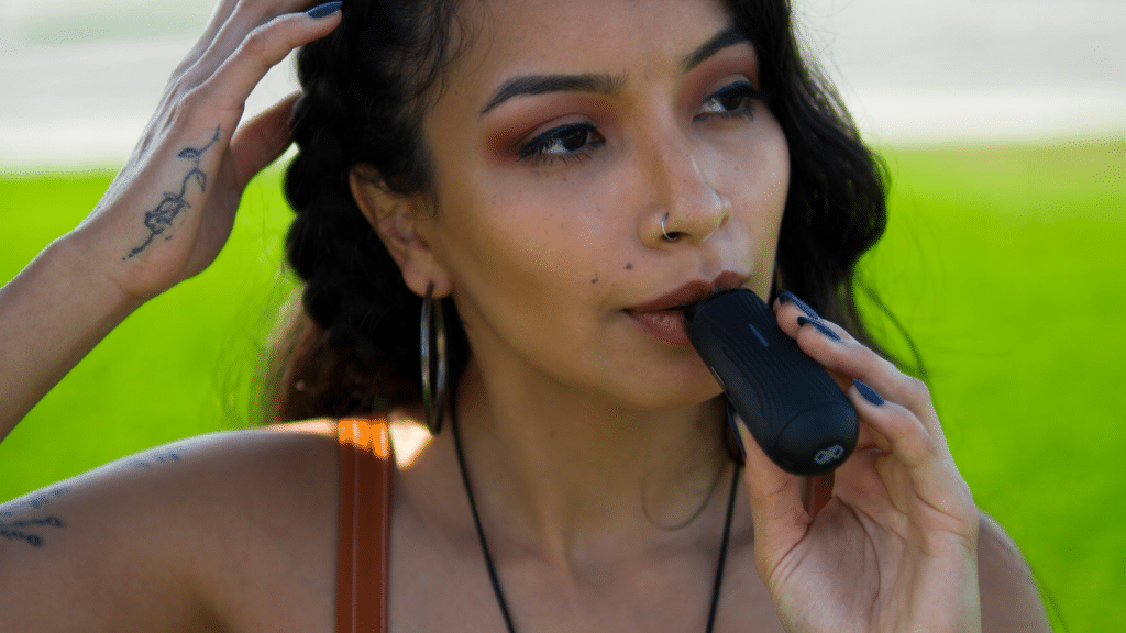 Girl taking a hit from the CFC Lite portable vaporizer.