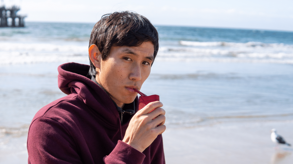 A guy taking a hit from the CFV vaporizer on a beach.