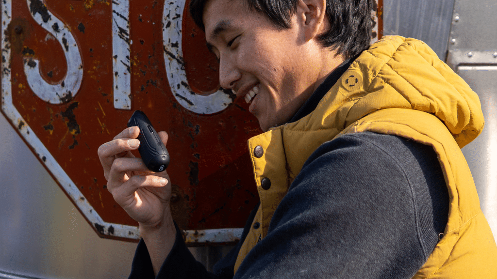 A guy smiles while holding his CFC Lite to adjust the temperature.