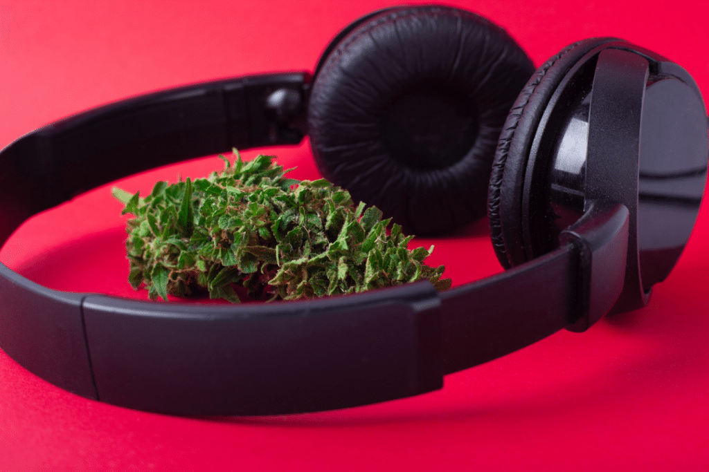 A pair of headphones with a cannabis nug next to them.