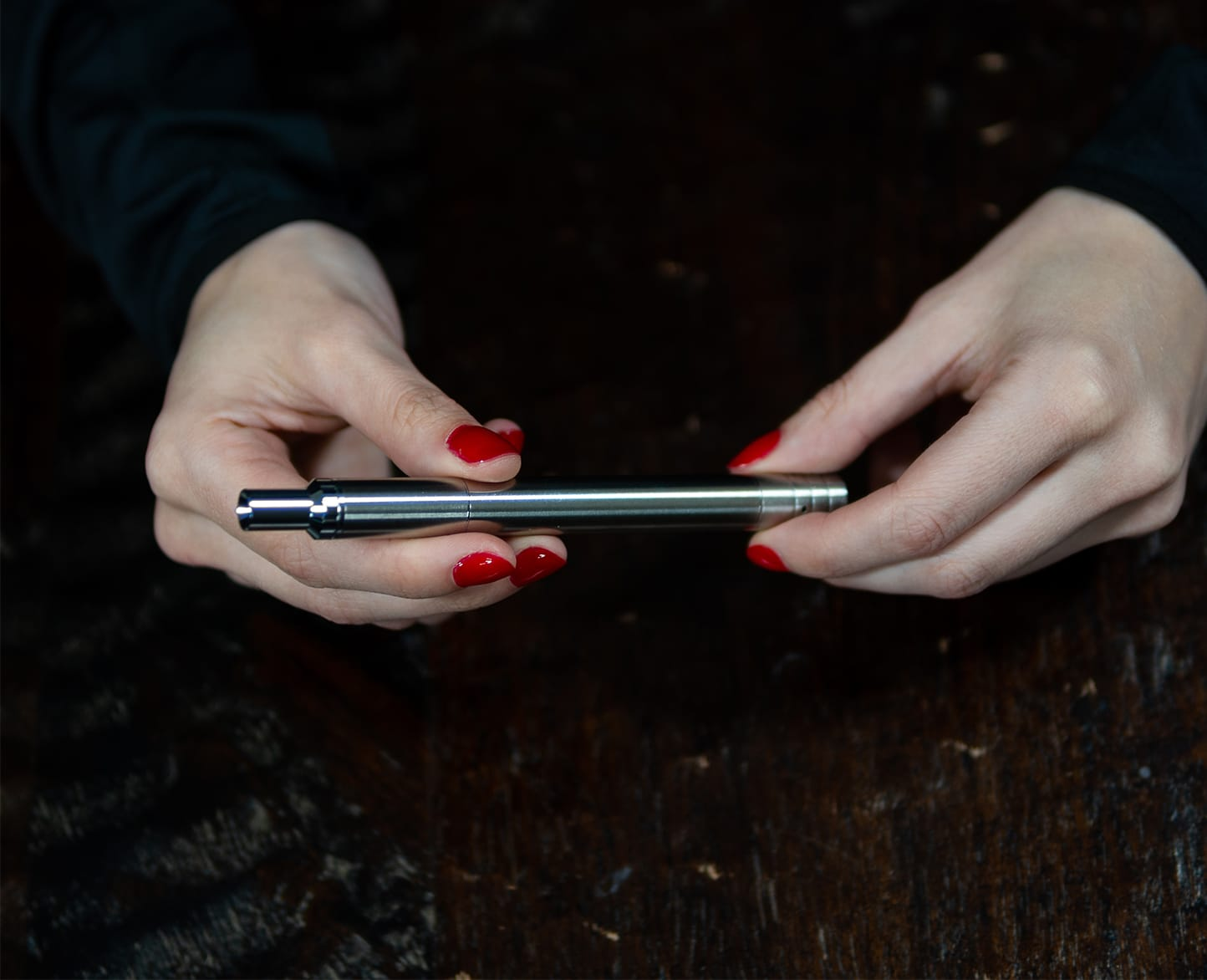Close-up of Two Hands with Red Fingernails Holding a Silver Terp Pen Sideways