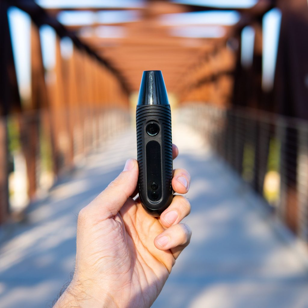 A hand holding the CFC 2.0 with a bridge in the background.