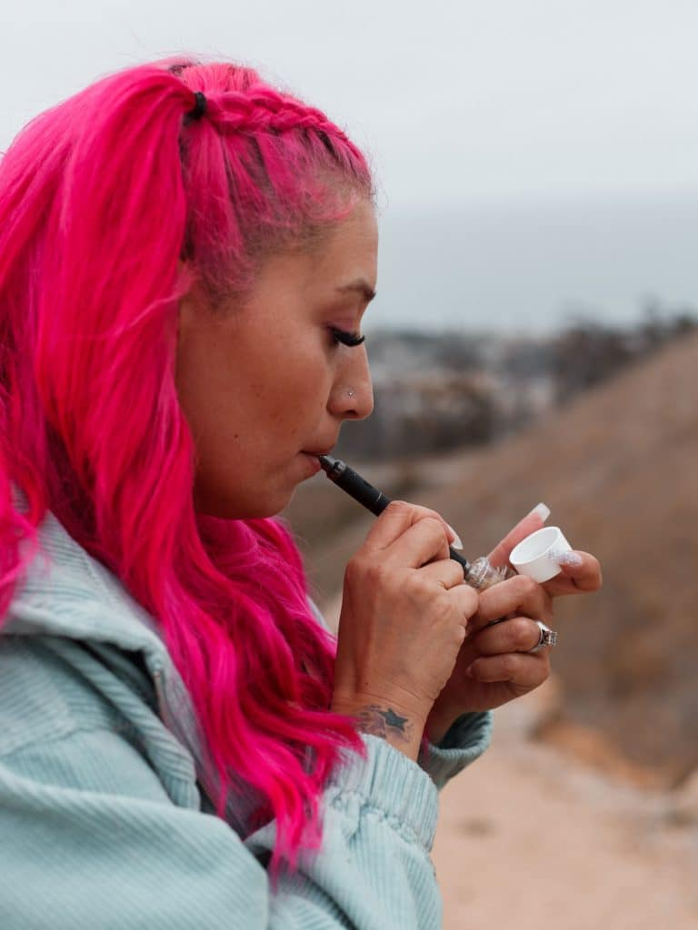 Cymba using the Terp Pen as a nectar collector, dabbing directly into her concentrate container.